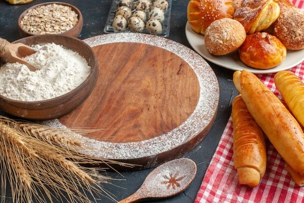 Vooraanzicht heerlijke zoete bagels met broodjes en bloem op donkere taartdeegcake zoete suiker