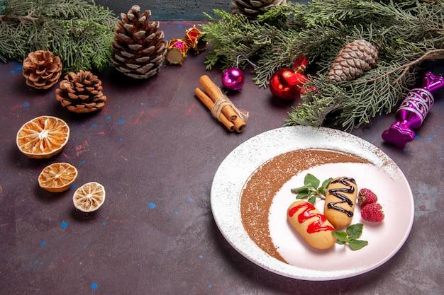 Vooraanzicht heerlijke zoete koekjes met kerstspeelgoed op donkere ruimte