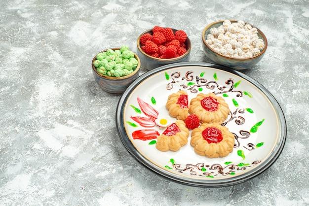 Vooraanzicht heerlijke zoete koekjes met rode gelei en snoepjes op witruimte