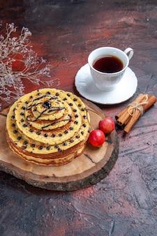 Vooraanzicht heerlijke zoete pannenkoeken met kopje thee op de donkere achtergrond