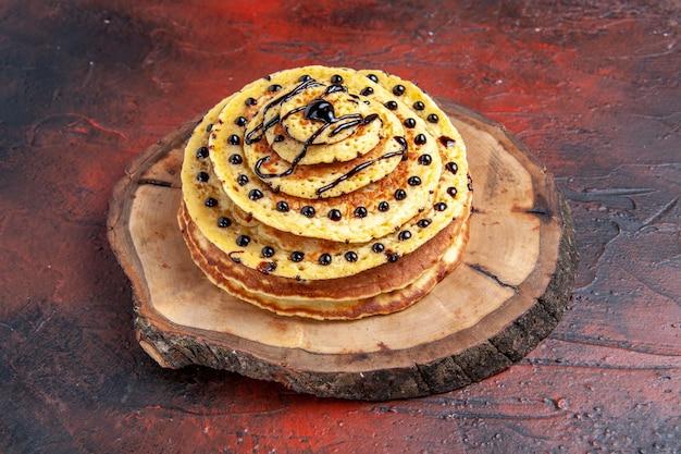 Vooraanzicht heerlijke zoete pannenkoeken met suikerglazuur op donkere achtergrond