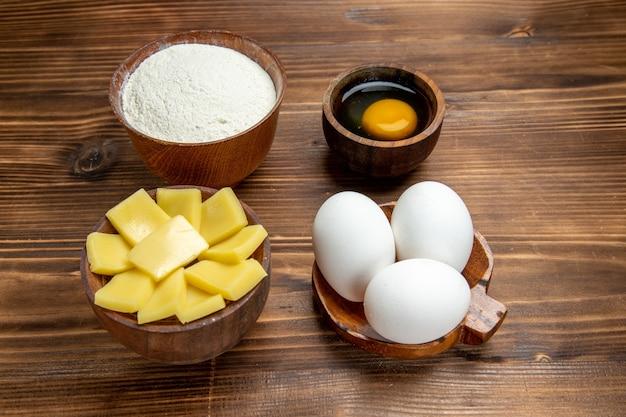 Vooraanzicht hele rauwe eieren met kaasmeel op bruin houten tafel product eierdeeg gebak