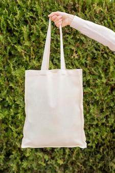 Vooraanzicht herbruikbare tas vastgehouden door vrouw hand in de natuur