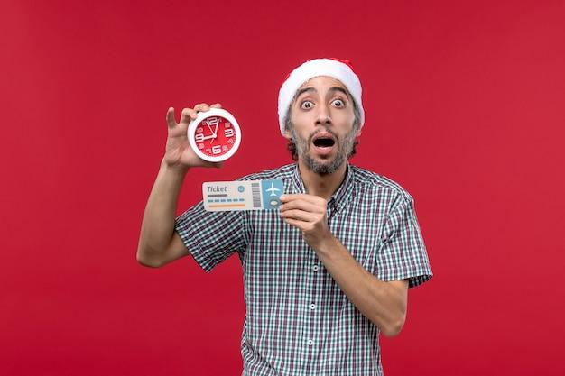 Vooraanzicht het jonge mannelijke kaartje met klok op rode achtergrond