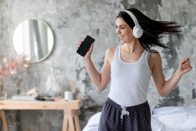 Vooraanzicht het jonge vrouw genieten die aan muziek luisteren