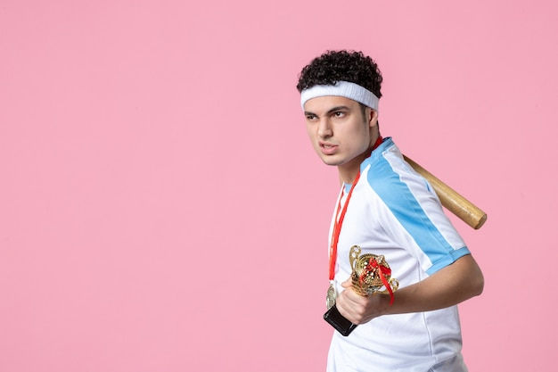 Vooraanzicht honkbalspeler in sportkleding met gouden beker en medaille