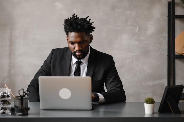 Vooraanzicht hoofd geschoten jonge glimlachende afro-amerikaanse zakenman die naar het scherm van de laptop kijkt