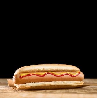 Vooraanzicht hotdog en zwarte exemplaar ruimteachtergrond