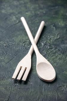 Vooraanzicht houten gebruiksvoorwerpen op een donkere achtergrond voedsel diner mes plastic keuken vork lepel foto bestek