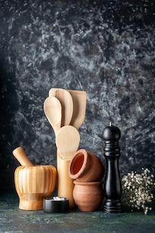 Vooraanzicht houten lepels met peperschudbeker op de donkere muur foto kleur keuken kruiden zout voedsel bestek