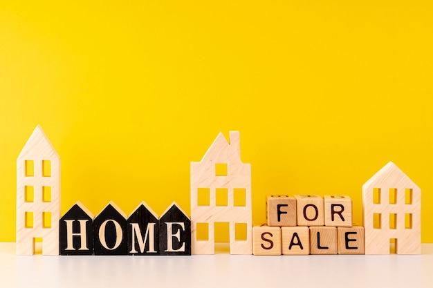 Vooraanzicht huis te koop belettering op gele achtergrond
