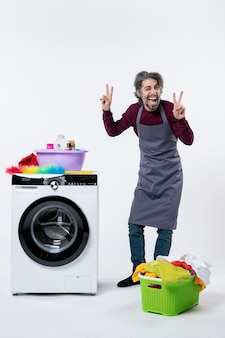 Vooraanzicht huishoudster man maken overwinning teken staande in de buurt van wasmachine wasmand op witte achtergrond