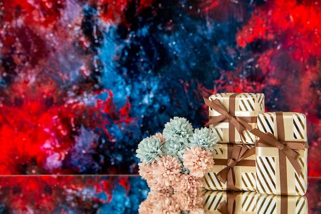 Vooraanzicht huwelijksgeschenken bloemen weerspiegeld op spiegel op donkerrode achtergrond
