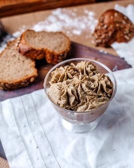 Vooraanzicht ijs chocolade in transparant plastic glas samen met verse sneetjes brood op de bruine vloer