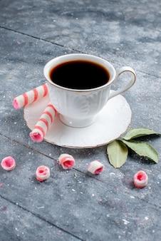 Vooraanzicht in de verte kopje koffie warm en sterk, samen met roze stok snoepjes op grijs