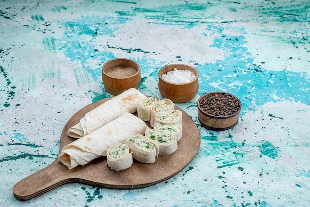 Vooraanzicht in de verte smakelijke groentebroodjes geheel en in plakjes gesneden met greens en kruiden op helderblauw bureau
