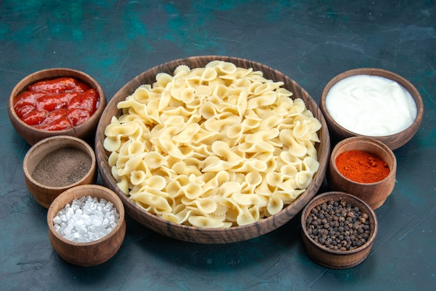 Vooraanzicht italiaanse pasta met verschillende kruiden op blauw