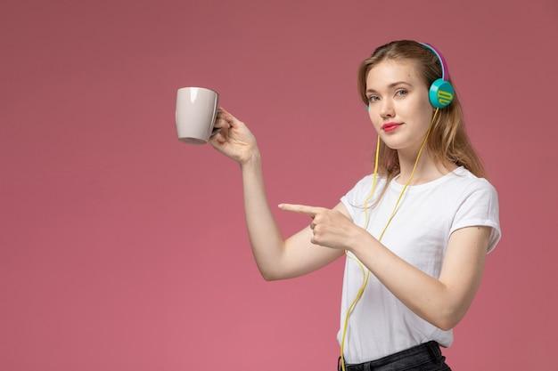 Vooraanzicht jong aantrekkelijk wijfje dat aan de kop van de muziekholding op de roze muur luistert modelkleur vrouwelijk jong meisje