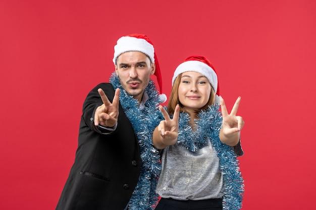 Vooraanzicht jong gelukkig paar in nieuwe jaarstemming op rode kerstmisliefde van de bureaukleur