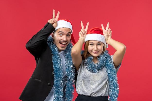 Vooraanzicht jong gelukkig paar in nieuwjaarsstemming op rode kerstmisliefde van de vloerkleur
