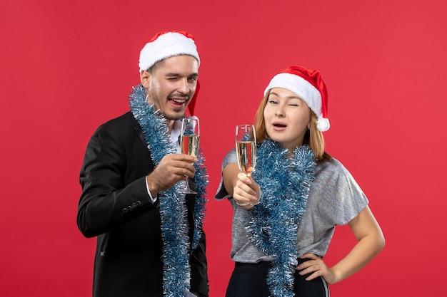 Vooraanzicht jong koppel alleen nieuw jaar vieren op rode muur kerst love party