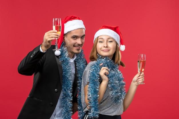 Vooraanzicht jong koppel net nieuwjaar vieren op rode muur liefde kerstfeest