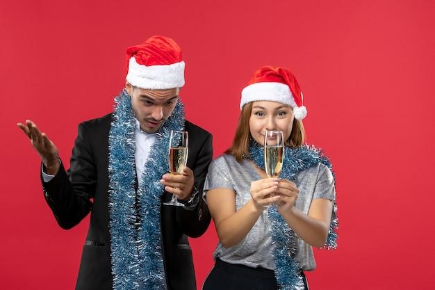Vooraanzicht jong koppel nieuwjaar vieren op rode bureau kerstfeest drankje liefde
