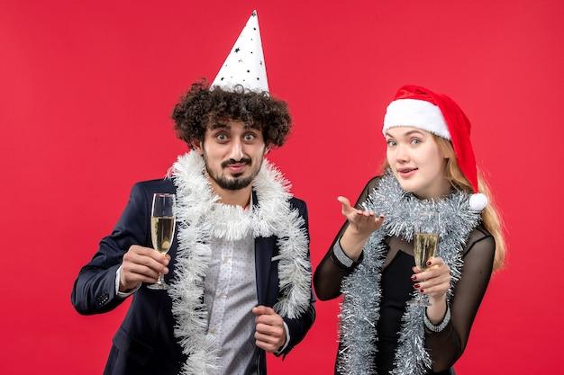 Vooraanzicht jong koppel nieuwjaar vieren op rode muur liefde kerstfeest