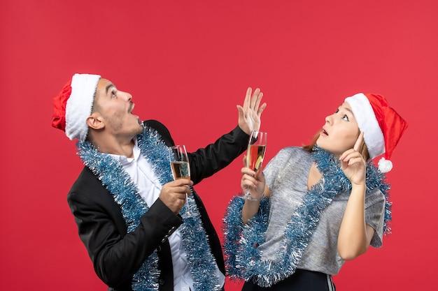 Vooraanzicht jong koppel nieuwjaar vieren op rode muur partij kerstmisliefde
