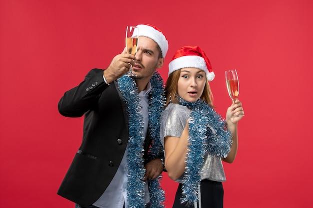 Vooraanzicht jong koppel nieuwjaar vieren op rode muur partij liefde kerst