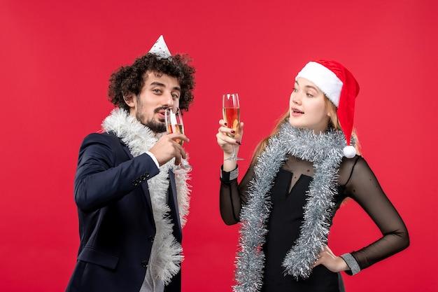 Vooraanzicht jong koppel nieuwjaar vieren op rode muur vakantie kerst liefde kleur