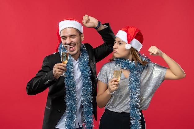 Vooraanzicht jong koppel nieuwjaar vieren op rode muur vakantie liefde kerst