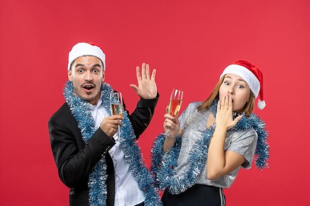 Vooraanzicht jong koppel nieuwjaar vieren op rode vloer partij kerst liefde