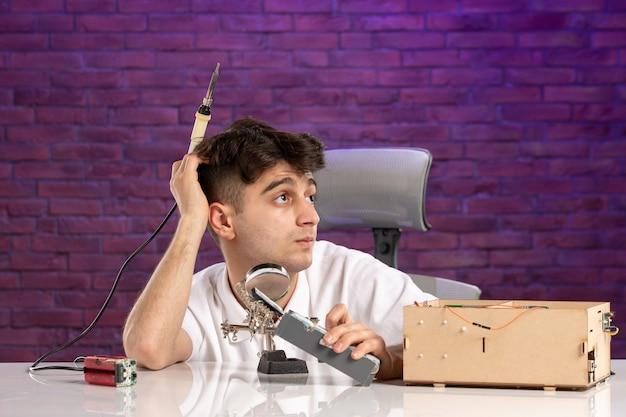 Vooraanzicht jong mannetje achter bureau dat kleine huislay-out op purpere muur probeert te bevestigen