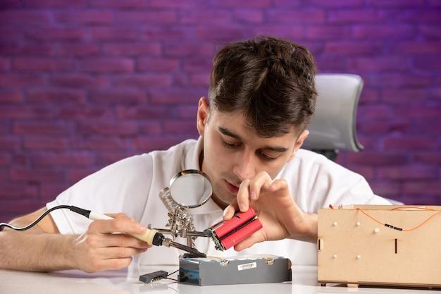 Vooraanzicht jong mannetje achter bureau dat kleine lay-out op purpere muur probeert te bevestigen