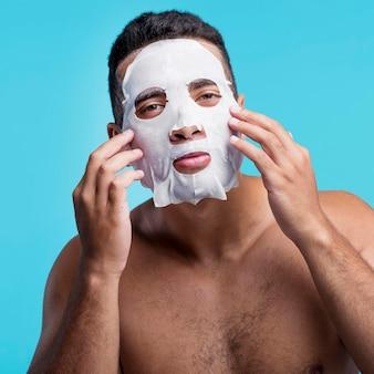 Vooraanzicht jong mannetje dat een gezichtsmasker toepast
