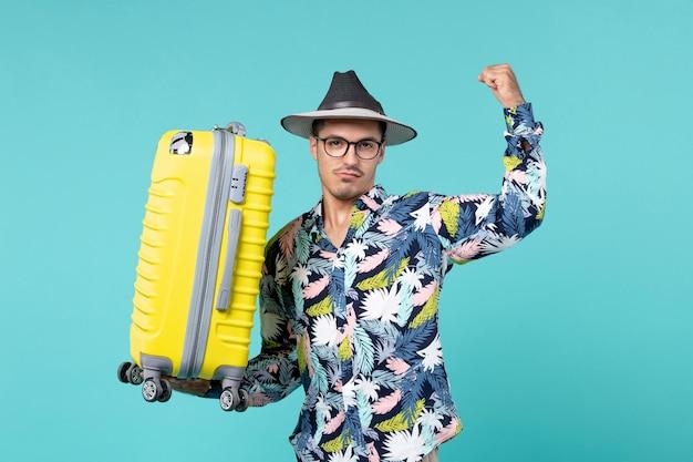 Vooraanzicht jong mannetje dat in vakantie gaat en zijn gele zak op blauw bureau houdt