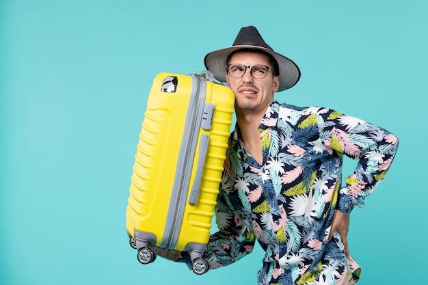 Vooraanzicht jong mannetje dat in vakantie gaat en zijn gele zak op blauwe ruimte houdt