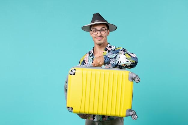Vooraanzicht jong mannetje dat in vakantie gaat en zijn zak op de blauwe ruimte houdt