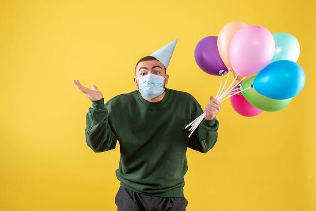 Vooraanzicht jong mannetje dat kleurrijke ballons in masker op geel houdt