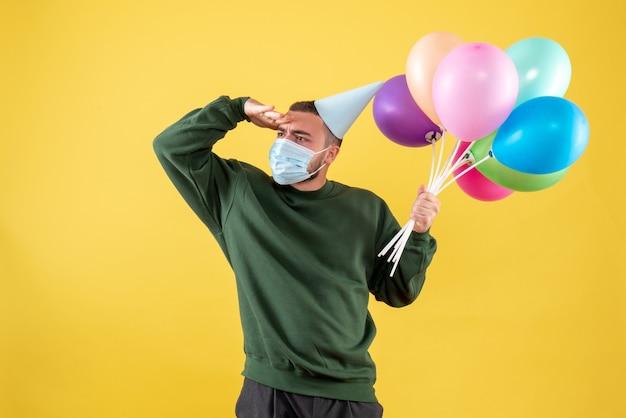 Vooraanzicht jong mannetje dat kleurrijke ballons in masker op gele achtergrond houdt