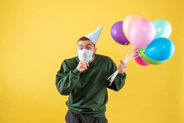 Vooraanzicht jong mannetje dat kleurrijke ballons in steriel masker op gele achtergrond houdt