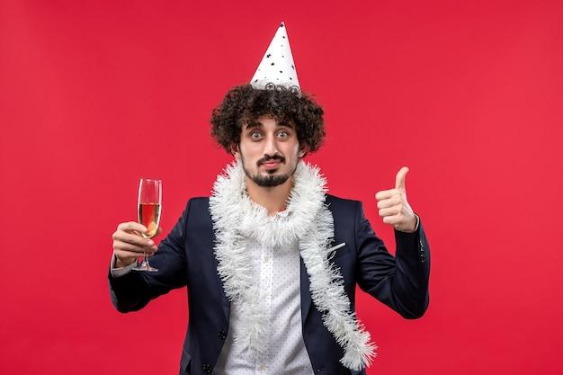 Vooraanzicht jong mannetje dat nieuw jaar viert dat op rode de partijkerstmis van de bureauvakantie komt
