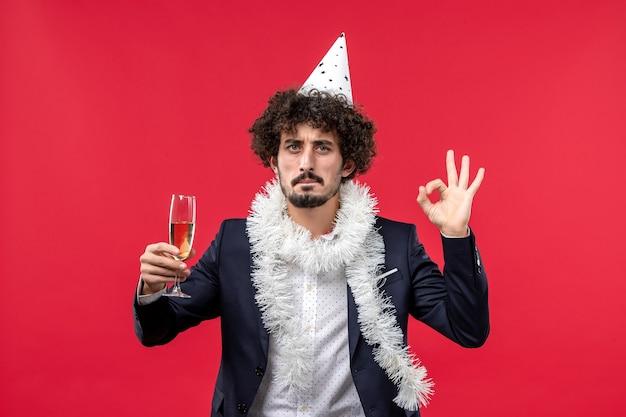Vooraanzicht jong mannetje dat nieuw jaar viert dat op rode de partijkerstmis van de vloervakantie komt