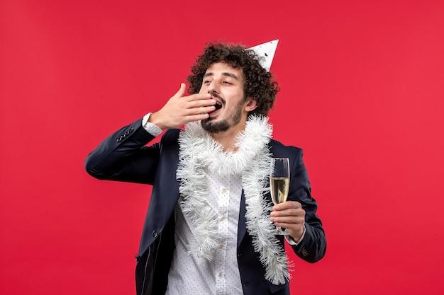 Vooraanzicht jong mannetje dat nog een jaar op rode muur menselijke vakantie kerstmis viert