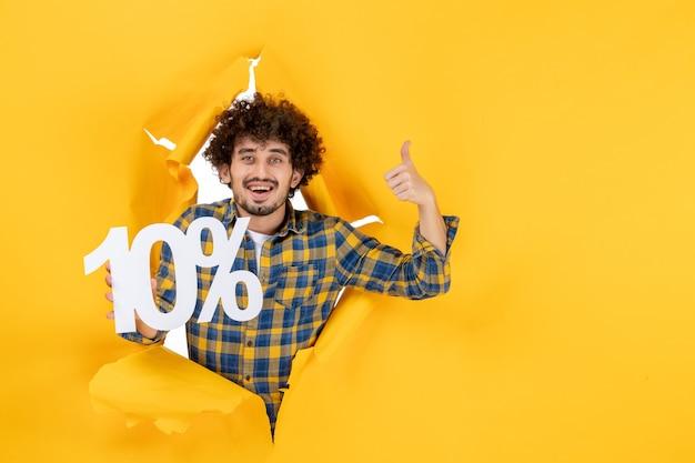 Vooraanzicht jong mannetje dat op gele achtergrond houdt