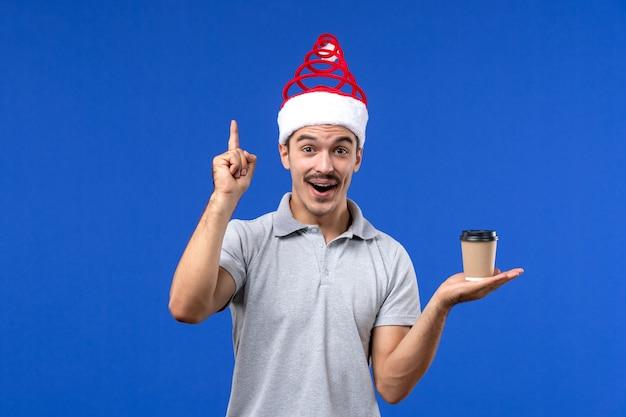 Vooraanzicht jong mannetje dat plastic koffiekop op een blauw bureau houdt emoties nieuwjaar mannetje