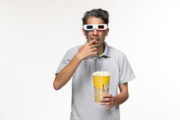 Vooraanzicht jong mannetje dat popcorn in d-zonnebril eet op wit bureau
