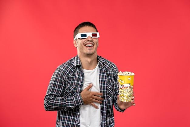 Vooraanzicht jong mannetje dat popcornpakket houdt en op lichtrode muur lacht mannelijke bioscoop bioscoop film leuke tijden