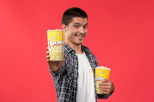 Vooraanzicht jong mannetje dat popcornpakketten houdt en op lichtrode muur glimlacht mannelijke bioscoop bioscoop film leuke tijden